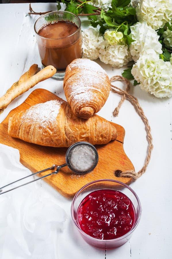 Tome o café da manhã com croissant frescos, vidro do café, leite, doce de morango e flores em um fundo de madeira branco fotografia de stock royalty free