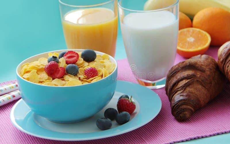Tome o café da manhã com flocos de milho, leite, croissant, suco de laranja e frutos frescos como a banana, as laranjas e as baga fotografia de stock royalty free