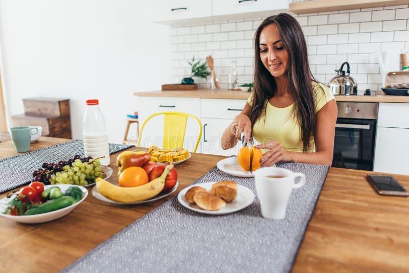 Tome o café da manhã com frutos, laranja, café e croissant Mulher que senta-se na tabela de cozinha fotos de stock
