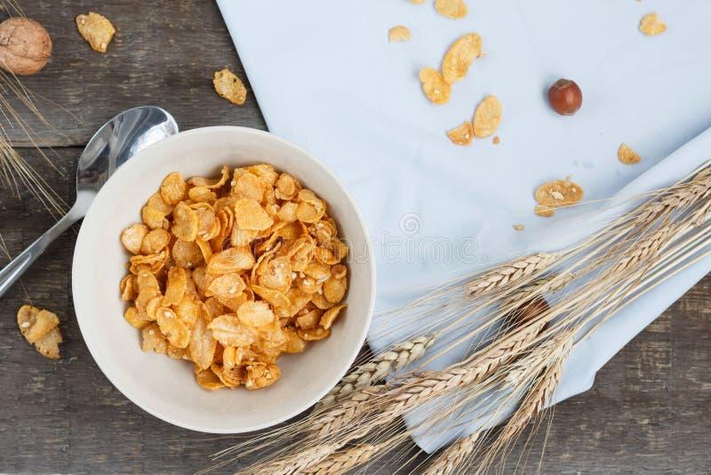 Tome o café da manhã com os flocos de milho com leite e suco de laranja em uma tabela de madeira fotografia de stock
