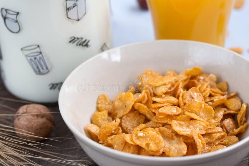 Tome o café da manhã com os flocos de milho com leite e suco de laranja em uma tabela de madeira foto de stock royalty free