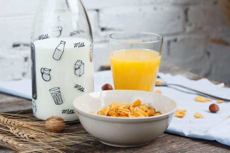 Tome o café da manhã com os flocos de milho com leite e suco de laranja em uma tabela de madeira imagem de stock royalty free