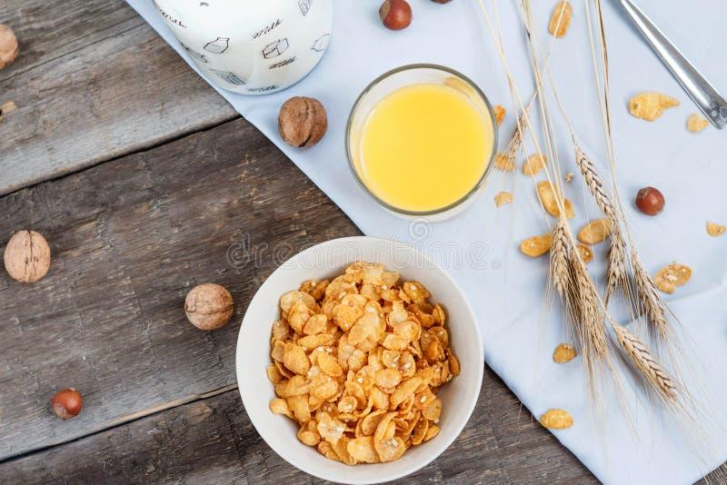 Tome o café da manhã com os flocos de milho com leite e suco de laranja em uma tabela de madeira fotos de stock royalty free