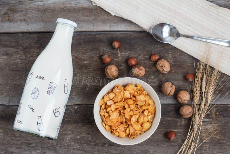 Tome o café da manhã com os flocos de milho com leite e suco de laranja em uma tabela de madeira foto de stock