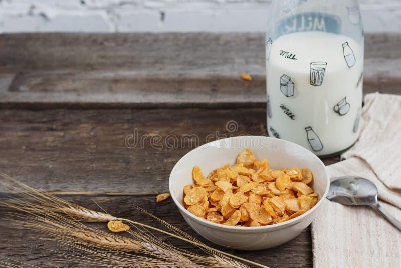 Tome o café da manhã com os flocos de milho com leite e suco de laranja em uma tabela de madeira fotografia de stock royalty free