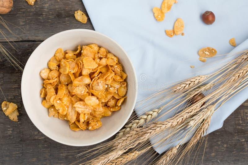 Tome o café da manhã com os flocos de milho com leite e suco de laranja em uma tabela de madeira imagens de stock royalty free