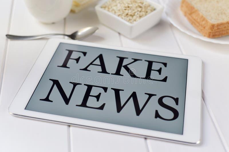 Tome o café da manhã e text a notícia falsificada em uma tabuleta fotos de stock