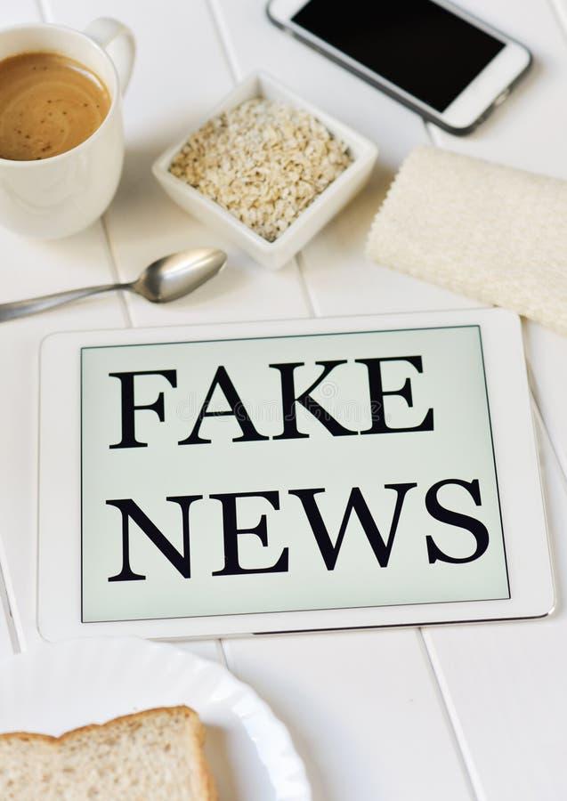 Tome o café da manhã e text a notícia falsificada em uma tabuleta imagens de stock