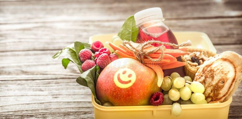 Tome o café da manhã ou almoce com o alimento saudável em uma caixa amarela, em um woode fotos de stock royalty free