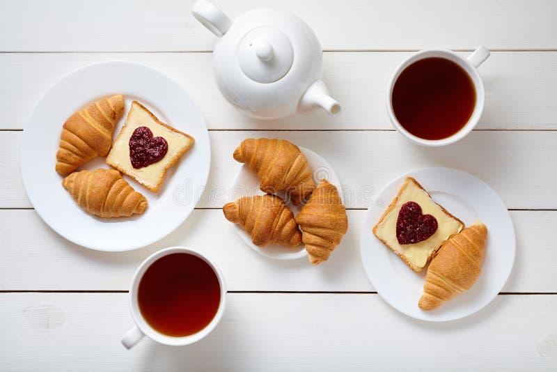 Tome o café da manhã para pares com brindes, doce, os croissant, e chá dados forma coração no fundo de madeira branco da tabela foto de stock