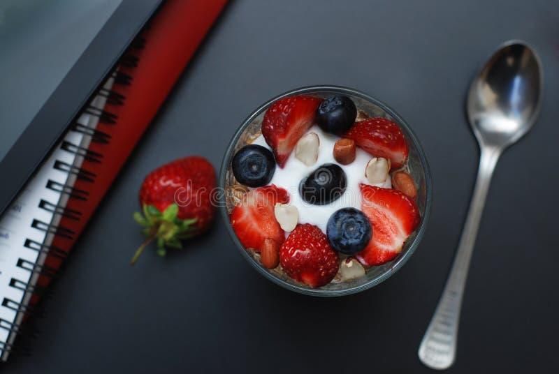 Tome o café da manhã para a saúde, morangos frescas, Blueberies, com a tabela do escritório do preto da farinha de aveia Tabuleta fotos de stock royalty free