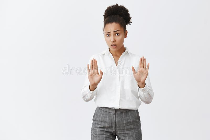 Tome-o fácil, amigo calmo da pena Afro-americano bonito preocupado fêmea na camisa branca e nas calças, puxando as palmas para foto de stock