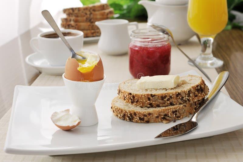 Tome o pequeno almoço com ovo quente e fatias de pão da farinha de aveia imagens de stock royalty free