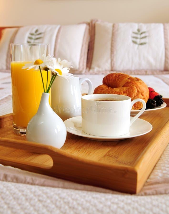 Tome o pequeno almoço em uma cama em um quarto de hotel fotografia de stock