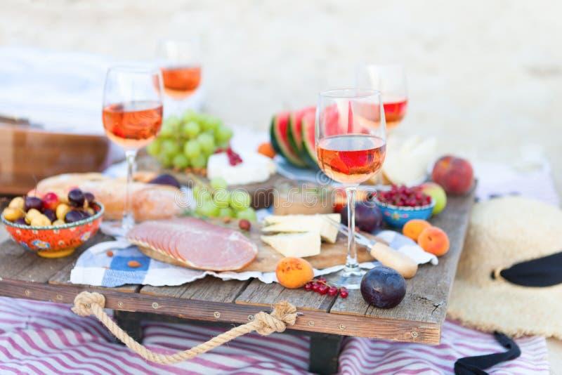 Tome parte num piquenique na praia no por do sol ao estilo da concep??o do boho, do alimento e da bebida foto de stock