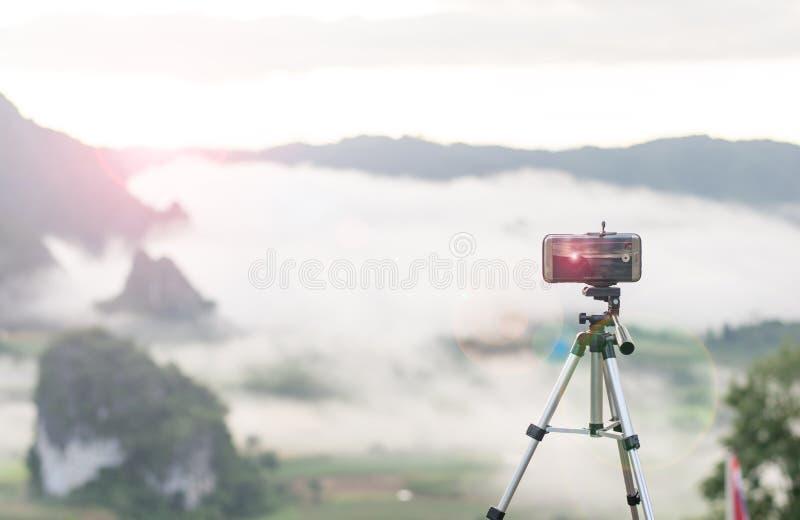 Tome una subida del sol de la foto por el teléfono fotografía de archivo