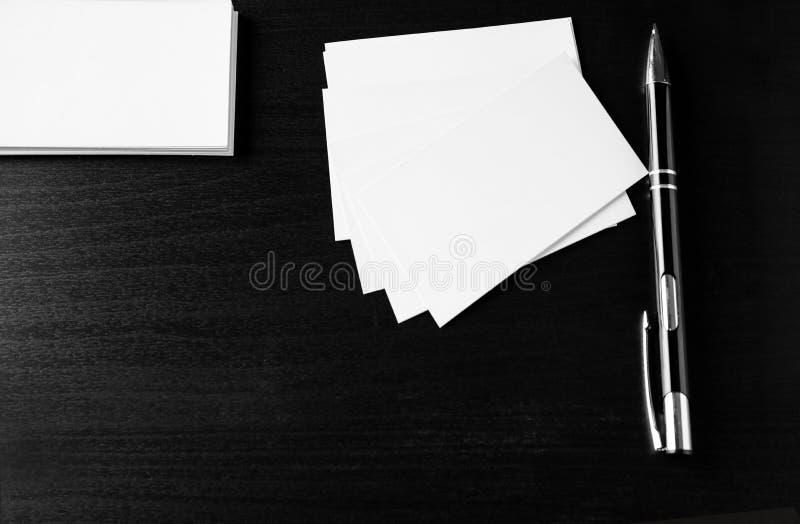 Tomma affärskort med pennan på mörk bakgrund arkivbild