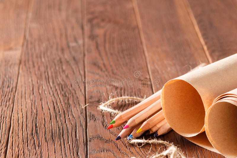 Tomma brunt pappers- och färgblyertspennor på trätabellen med det dekorativa repet arkivfoto