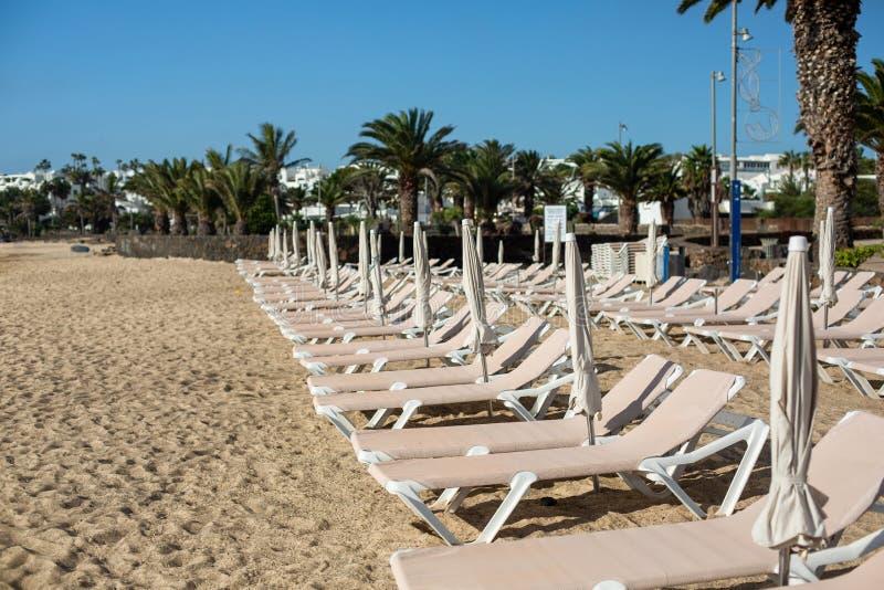 Tomma chaise-vardagsrum på stranden i staden av Costa Teguise royaltyfria foton