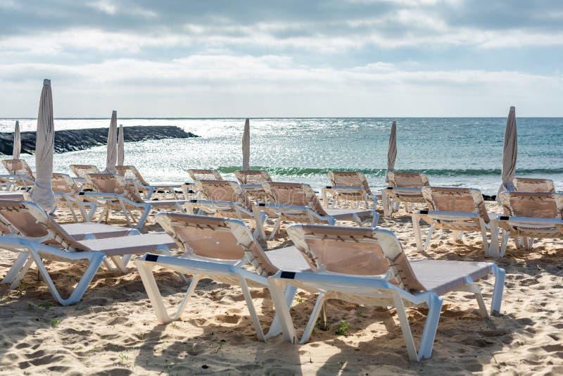 Tomma chaise-vardagsrum på stranden i staden av Costa Teguise arkivbild