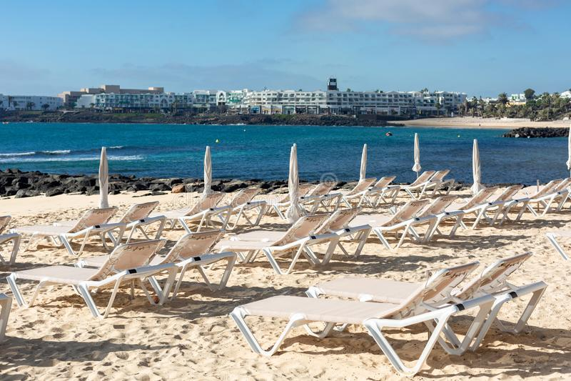 Tomma chaise-vardagsrum på stranden i staden av Costa Teguise arkivfoton