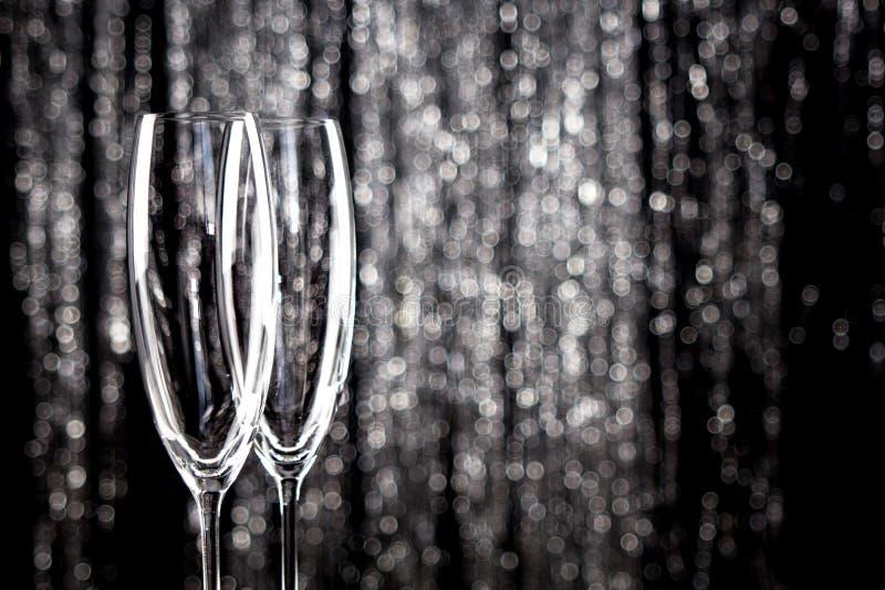 Tomma champagne- eller vinexponeringsglas med blänker julglittergarnering på bakgrund royaltyfri bild