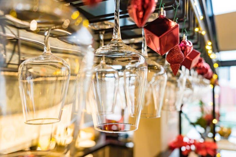 Tomma exponeringsglas av vin ovanför en stång rack på juldecoratien royaltyfri bild