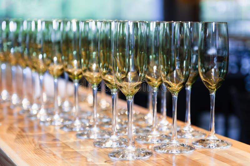 Tomma exponeringsglas för vitt vin beställde i symmetri på en countertop royaltyfri fotografi
