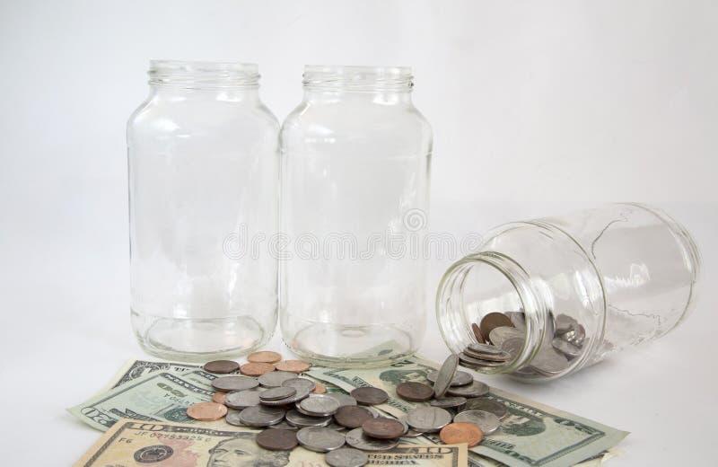 Tomma exponeringsglaskrus och pengar royaltyfri bild