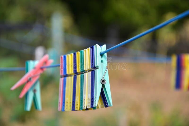 Tomma färgrika klädnypor på rad i trädgård arkivfoton