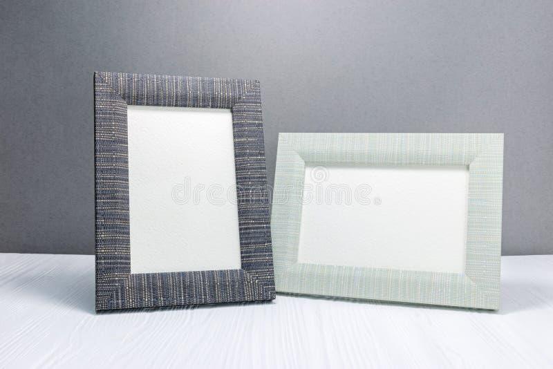 Tomma fotoramar på det vita träskrivbordet mot grå väggbackgr royaltyfria bilder