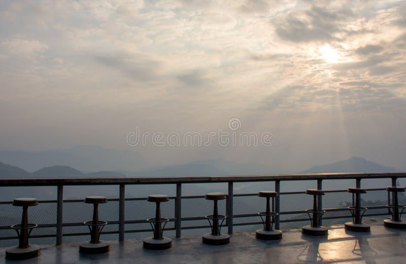 Tomma gamla wood stångräknare- och stolstolar med bergsikt och härlig himmel i morgonen arkivfoto