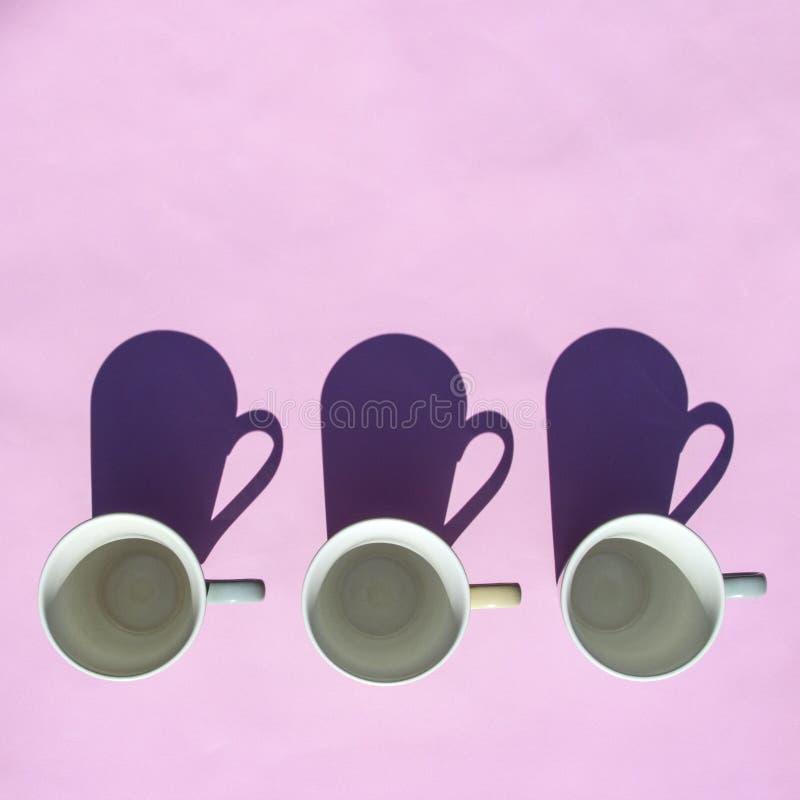 Tomma kaffe- och tekoppar står i rad på rosa bakgrund i solljus med skuggor B?sta sikt, lekmanna- l?genhet Minsta stil Isolerat p royaltyfri foto
