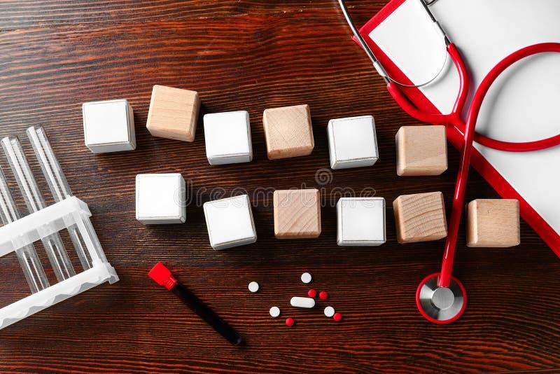 Tomma kuber med stetoskop- och blodprövkopian på träbakgrund royaltyfri bild