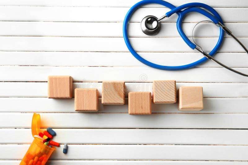 Tomma kuber med stetoskopet och piller på vit träbakgrund royaltyfri foto