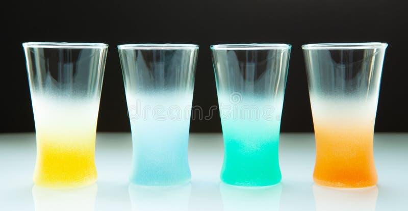 Tomma kulöra exponeringsglas för olika drinkar på en mörk bakgrund royaltyfri fotografi