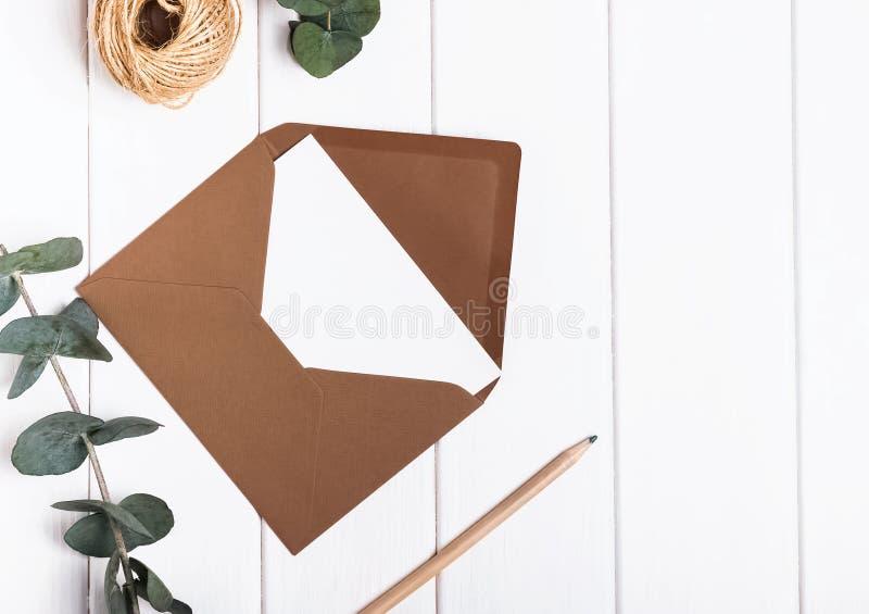 Tomma kuvert-, blyertspenna- och eukalyptusfruncher på den vita tablen royaltyfria bilder