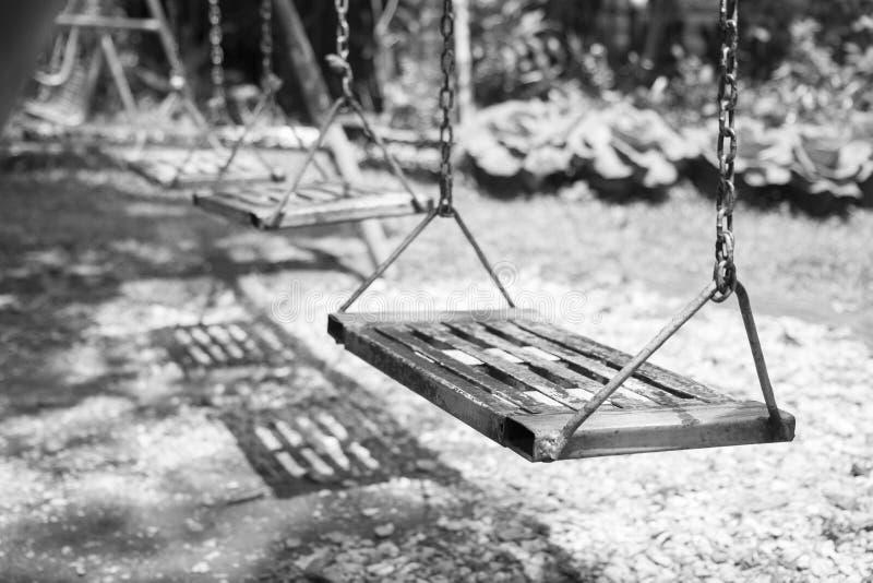 tomma lekplatsswings vingar i stad parkerar Tomma kedjegungor i sommar lurar barnlekplatsen royaltyfri foto