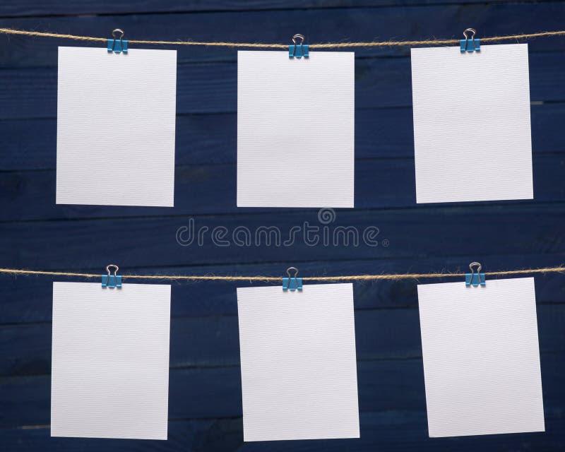 Tomma pappers- kort som fästas med färgrika gem på linnerep på bakgrunden av i suddighetsdet träblåa brädet, tomma mallar för royaltyfria foton