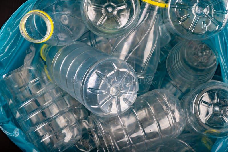 Tomma plast- flaskor i en avskrädepåse Hushållavfalls som samlas i en blå påse royaltyfria foton