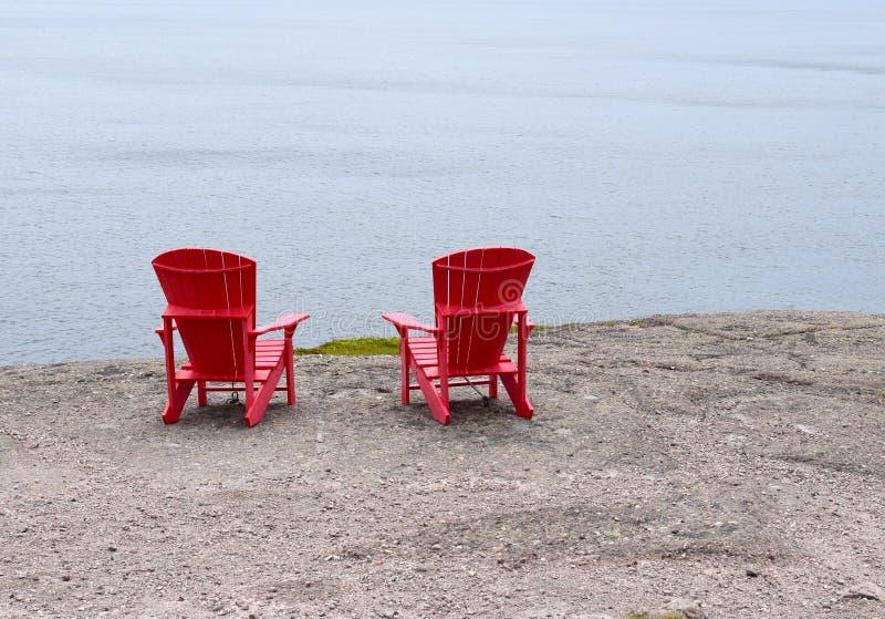 Tomma röda Adirondack stolar på kanten av en klippa fotografering för bildbyråer