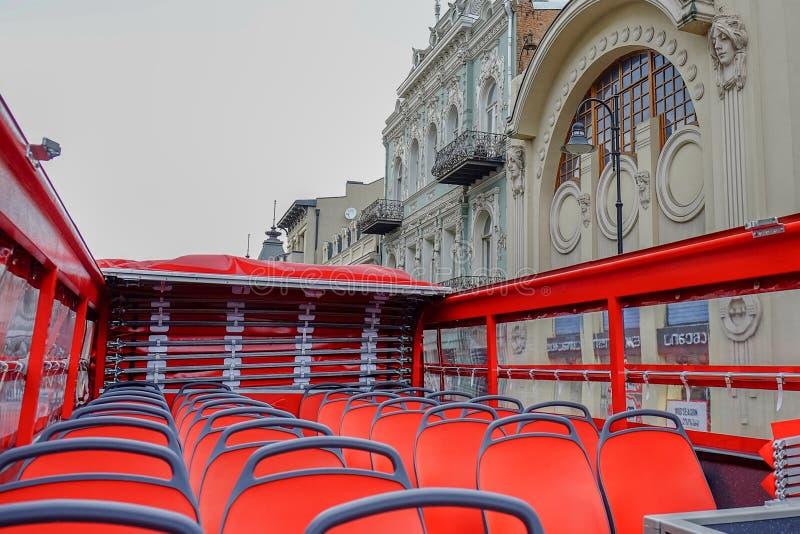 Tomma röda platser av den röda turist- bussen för dubbel däckare Inga handelsresande och besökare för stad turnerar i otäck molni royaltyfria foton