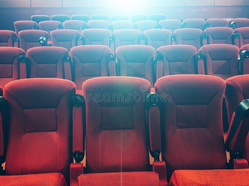 Tomma rader av röda stolar i bio eller teatern i blått projektorljus royaltyfri fotografi
