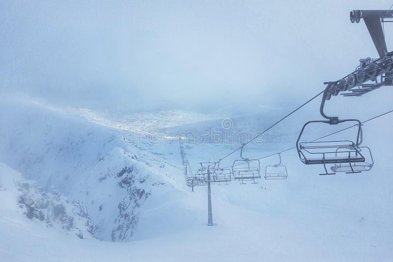 Tomma skidliftar bland snö-täckte berg och snödrivor, skidar lutningar göras klar inte och inte klart för turister arkivfoton