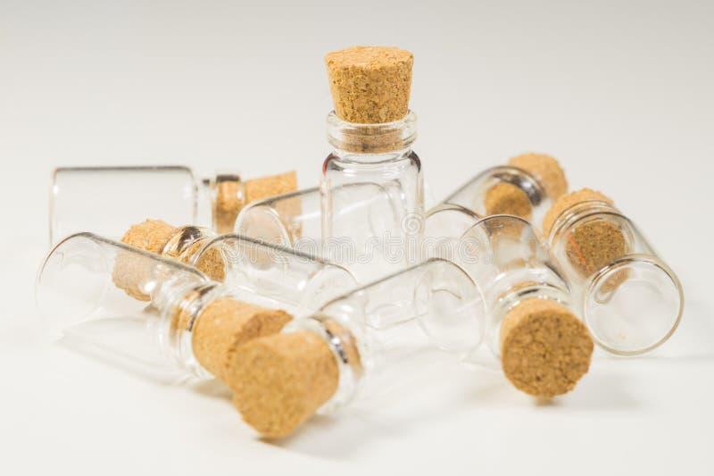 Tomma små flaskor med korkproppen som isoleras på vit genomskinliga behållare bakgrund vita isolerade provr?r arkivfoto