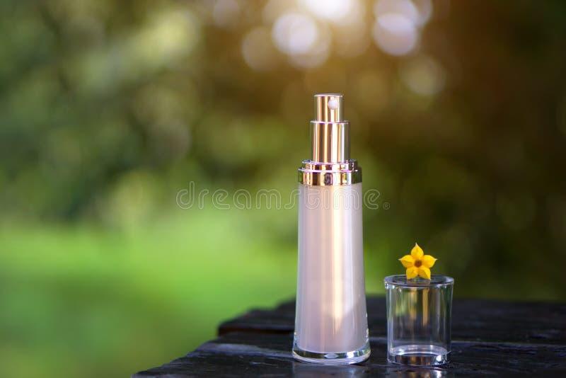 Tomma sprejskönhetsmedelflaskor - modell med gräsplan- och bokehbackg arkivbild