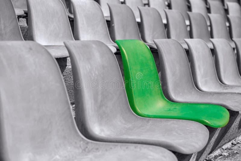 Tomma svartvita plast-stolar på arenan med en i Co royaltyfria bilder