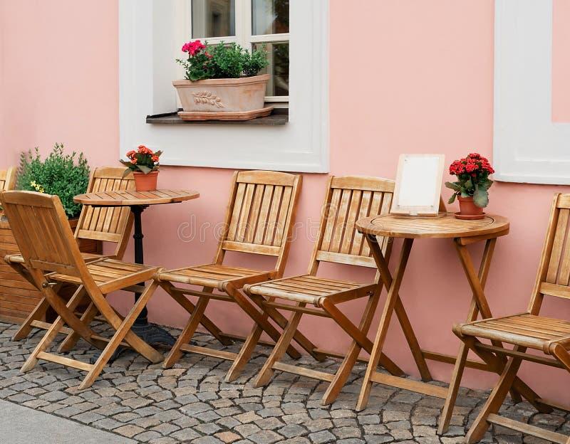 Tomma tabeller för utomhus- kafé längs en Prague kullerstengata arkivfoton