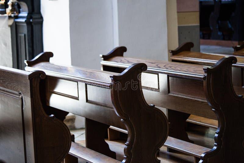 Tomma träbänkar i katolsk kyrka arkivfoto