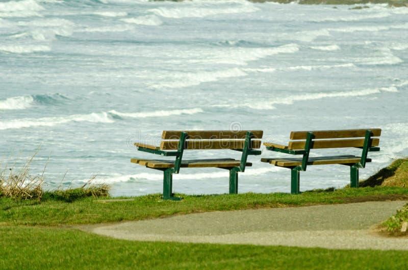 Tomma två parkerar bänkar som ser havssikt fotografering för bildbyråer